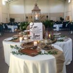 3 round draped tables clustered together and set up for a wedding reception